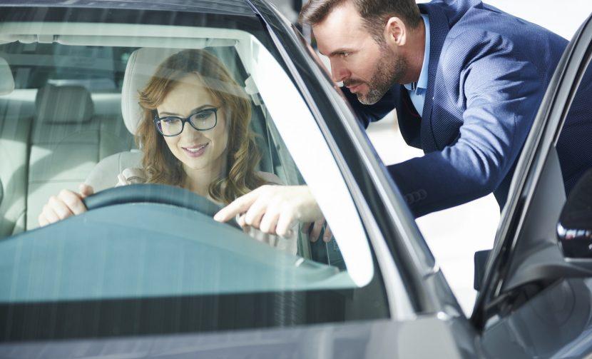 Couple of customers examining new car